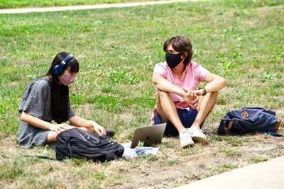 Two masked students sit on grass on North Campus at UMass Lowell.