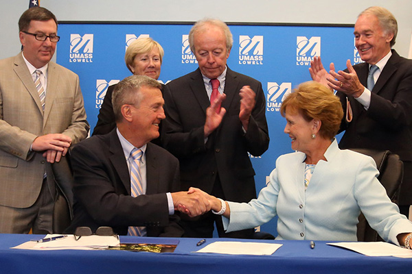 Lowell city manager Kevin Murphy and UMass Lowell chancellor Jacquie Moloney sign a master agreement formalizing the contributions UML will make to the city. Looking on, from left, State Rep. Dave Nangle, State Sen. Eileen Donoghue, Lowell mayor Ed Kennedy and U.S. Sen. Ed Markey.
