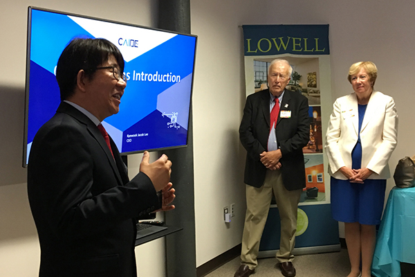 CAIDE Systems Founder and CEO Kyewook Jacob Lee explains his company s technology while officials, including Mayor William Samaras and City Manager Eileen Donoghue, listen.
