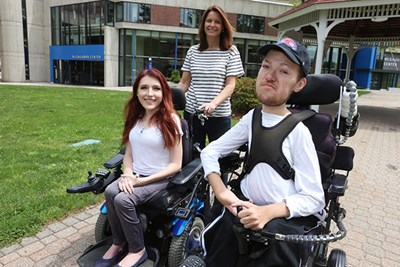 UMass Lowell senior Nicholas Raymond, 22, his sister Elizabeth, both in wheelchairs, and their mother, Kathy, outside on South Campus.