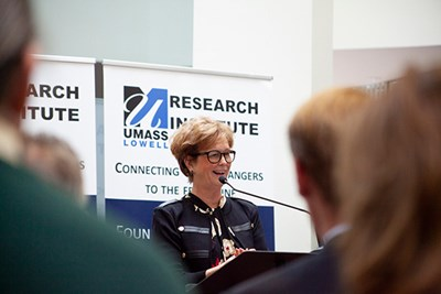 UMass Lowell Chancellor Jacquie Moloney at podium at Research Institute in Lincoln.