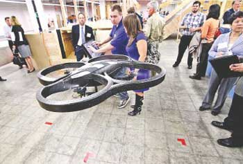 A flying robot, demonstrated by UMass Lowell student Jordan Allspaw for Cherie Comeau of Middlesex Community College's corporate education and training department, was on display at Thursday's UMass Lowell robotics event.