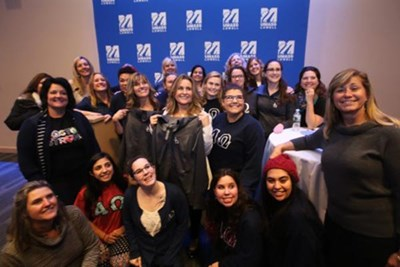 Boston Marathon bombing survivor Roseann Sdoia, center in white jacket, poses with current and former members of Alpha Omega, the UMass Lowell sorority she was in, after speaking at University Crossing Thursday.