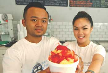 Nyden Heng, left, and his fiancee, Jennifer Ho, show off their Asian-inspired treat, shaved snow, at their new Lowell business, Snowdaes.