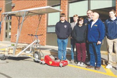 Students and teachers stand with solar mower