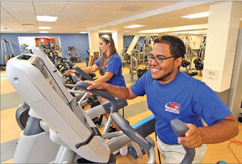 Courtney Dias, 22, of Milford, and Jimmy Ortiz, 22, of Lawrence, both living-learning community resident advisers at Riverview Suites at UMass Lowell, try out the exercise equipment in the new building s fitness center on Friday.