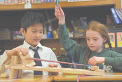 Lowell Catholic third-graders Tyson Pham and Irene Early operate a small weaving loom