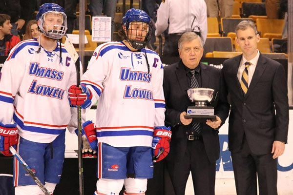UMass Lowell players A.J. White and Michael Kapla, and head coach Norm Bazin, right, accept the Hockey East runner-up trophy from Hockey East Commisioner Joe Bertagna Saturday night.