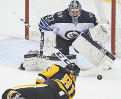 Winnipeg Jets goaltender Connor Hellebuyck prepares to make a glove save on Penguins star Phil Kessel.