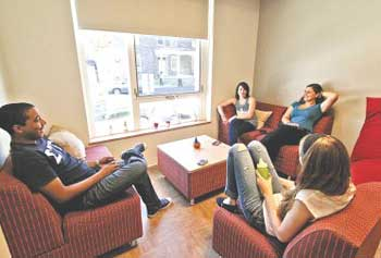 From left, UMass Lowell students Nathan Pizarro, 20, Chelsey Pepin, 20, Emmeline Aroush, 19, and Eilish Faherty, 19, relax in one of the dorms in the new University Suites which opened Thursday.