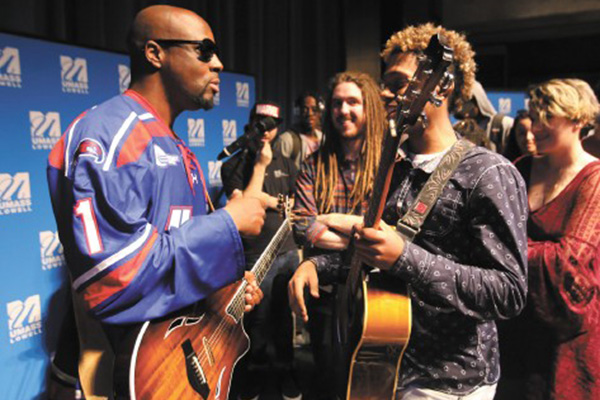 JAM SESSION: Pop star Wyclef Jean meets with UMass Lowell music students at the Thursday Recital Hour/Applied Seminar. Here, Lowell High junior Brian Terrero, 17, talks with Jean after the event.