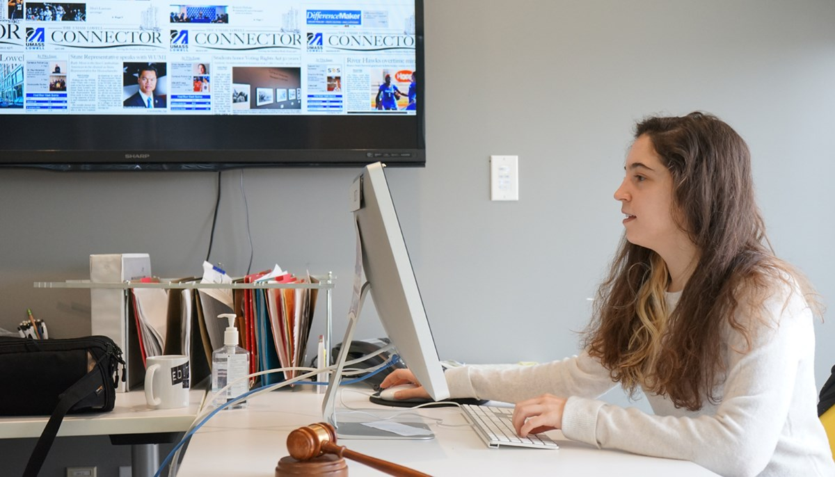 Taylor Carito, editor-in-chief of UMass Lowell's student newspaper The Connector, sits in The Connector office and works on a computer.