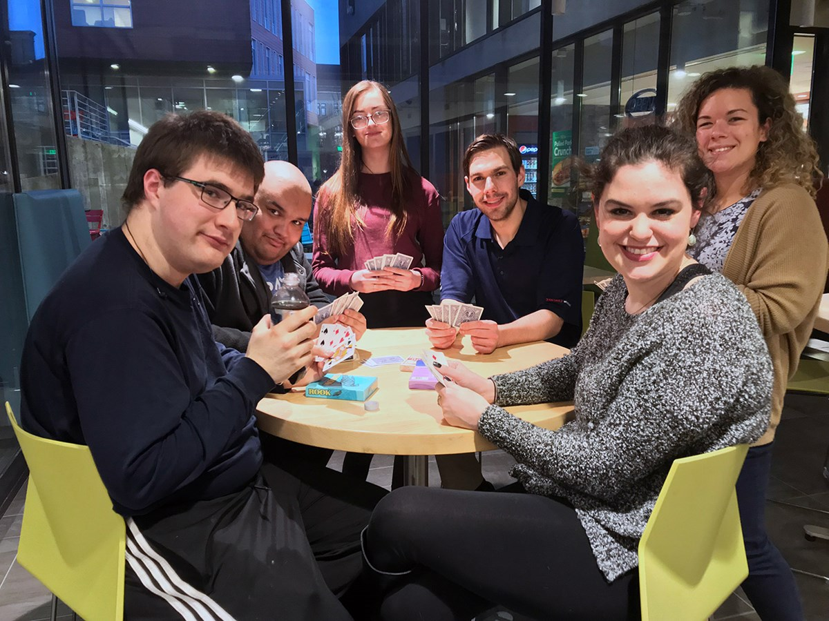 "Group photo of ""The Network"" showing young men and women sitting around a table playing cards. The Network is a monthly social networking program for high functioning adolescents and young adults on the autism spectrum aged between 16-30 years. The goal is to provide those with ASD an opportunity to meet others and hopefully make connections."