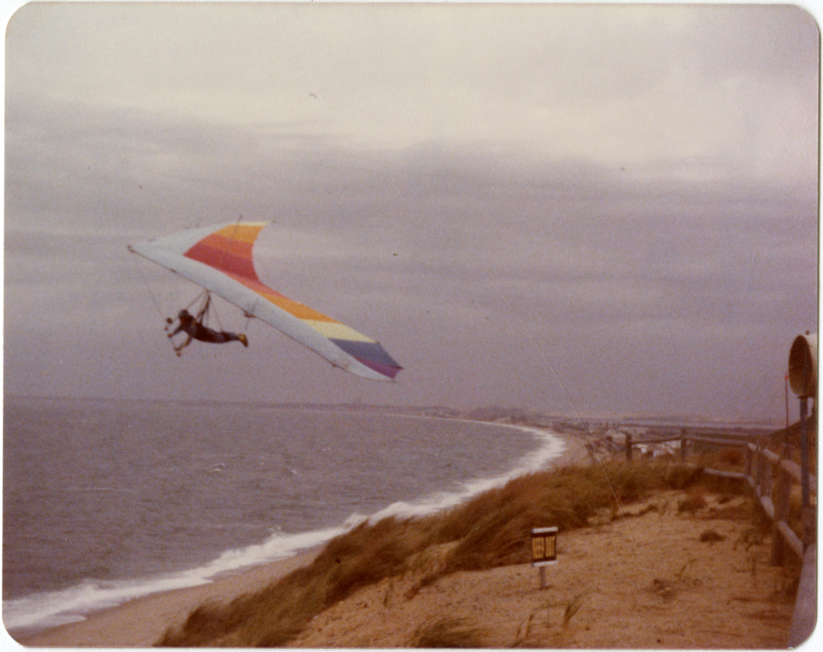 An old color photo of a hang glider soaring over a beach