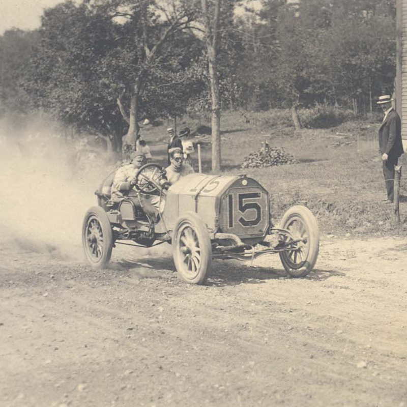A driver racing down the Merrimack Valley Auto Course in 1908, which began and ended on Pawtucket Boulevard along the Merrimack River
