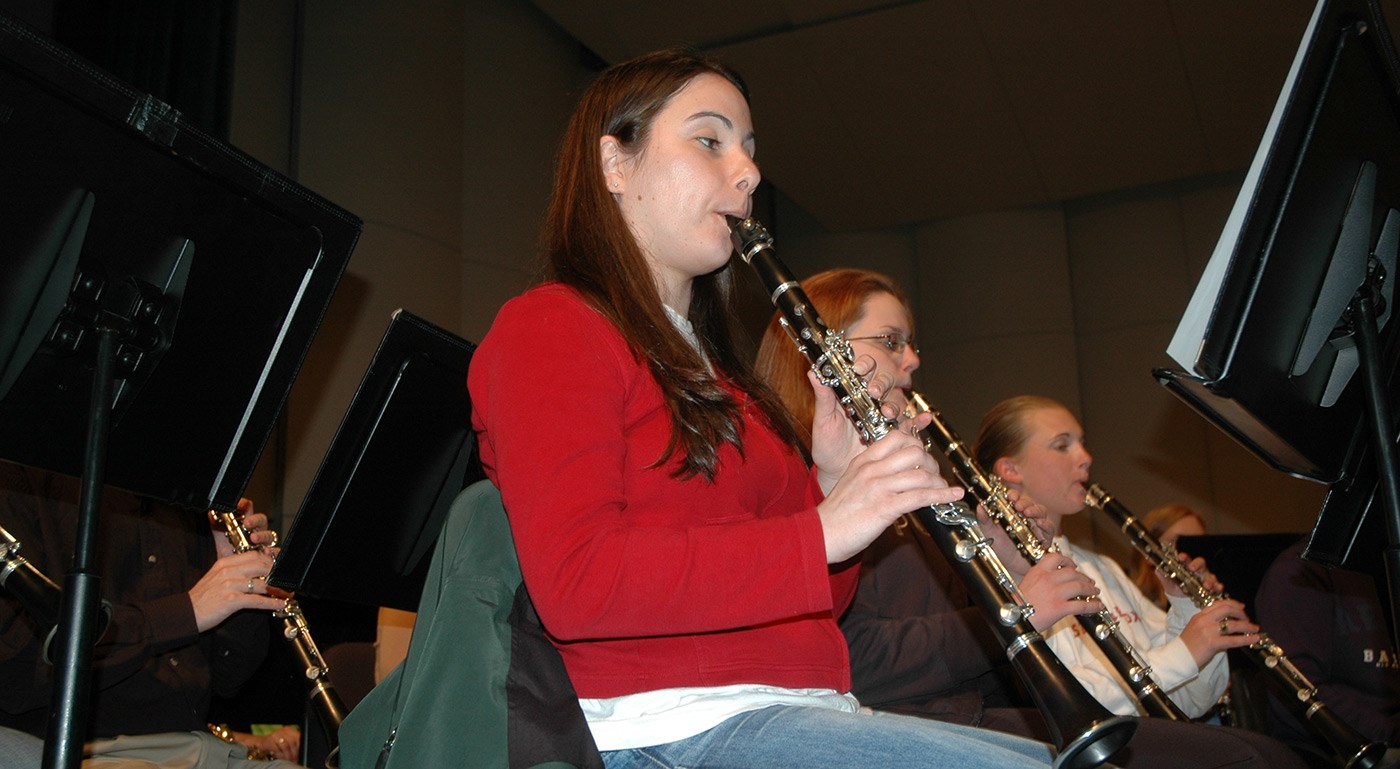 Three female students playing clarinets in a music class/rehearsal.