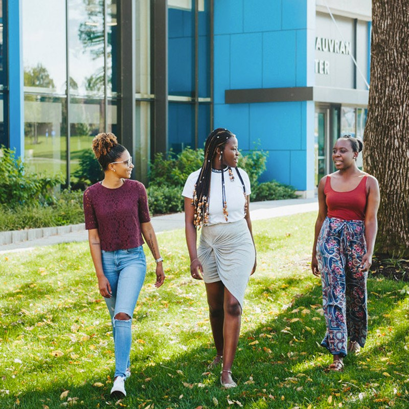 three female students walking on UMass Lowell south campus
