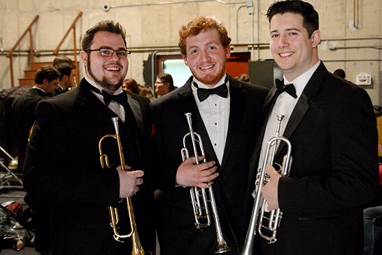 three-male-students-pose-trumpets-tuxedos