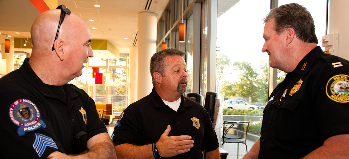 "UMass Lowell police officers talk with a city of Lowell police officer during the ""Coffee with a Cop"" event at University Crossing."