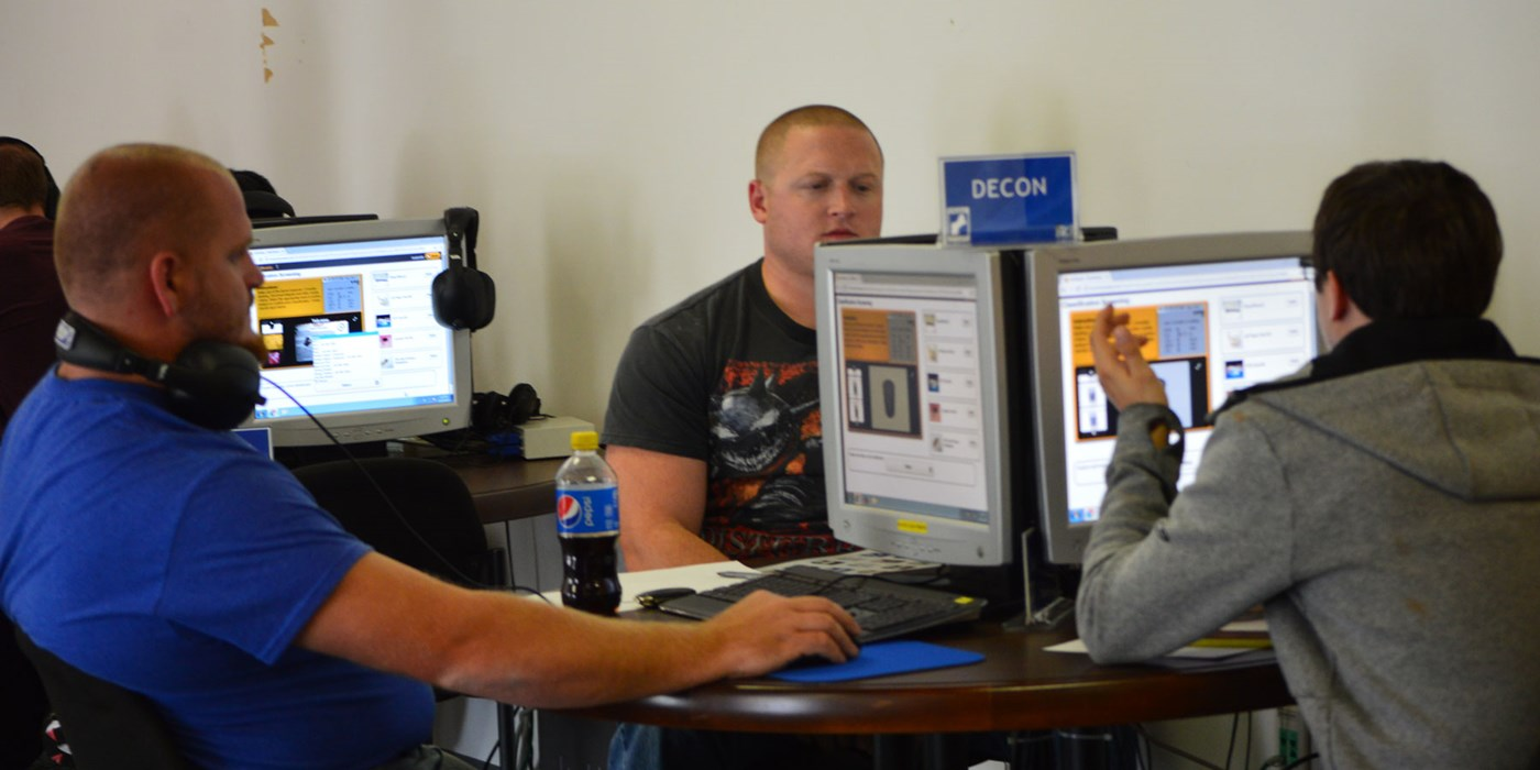 Students sit around a desktop computer working on a simulation of an actual hazardous spill at a warehouse. The students are required to work together to clean up the simulated hazardous spill.
