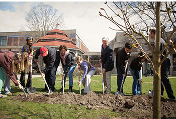 Students join Chancellor Marty Meehan in planting a Briotii red horse chestnut tree on South Campus at the start of Earth Week observances. The tree was dedicated to Boston Marathon bombing victims.