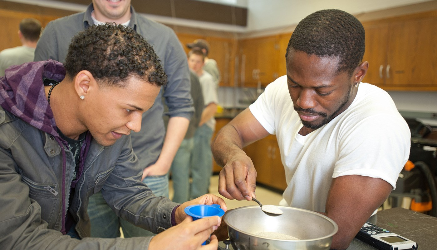 Two African American male UMass Lowell students working in a Civil & Environmental Engineering lab or class.