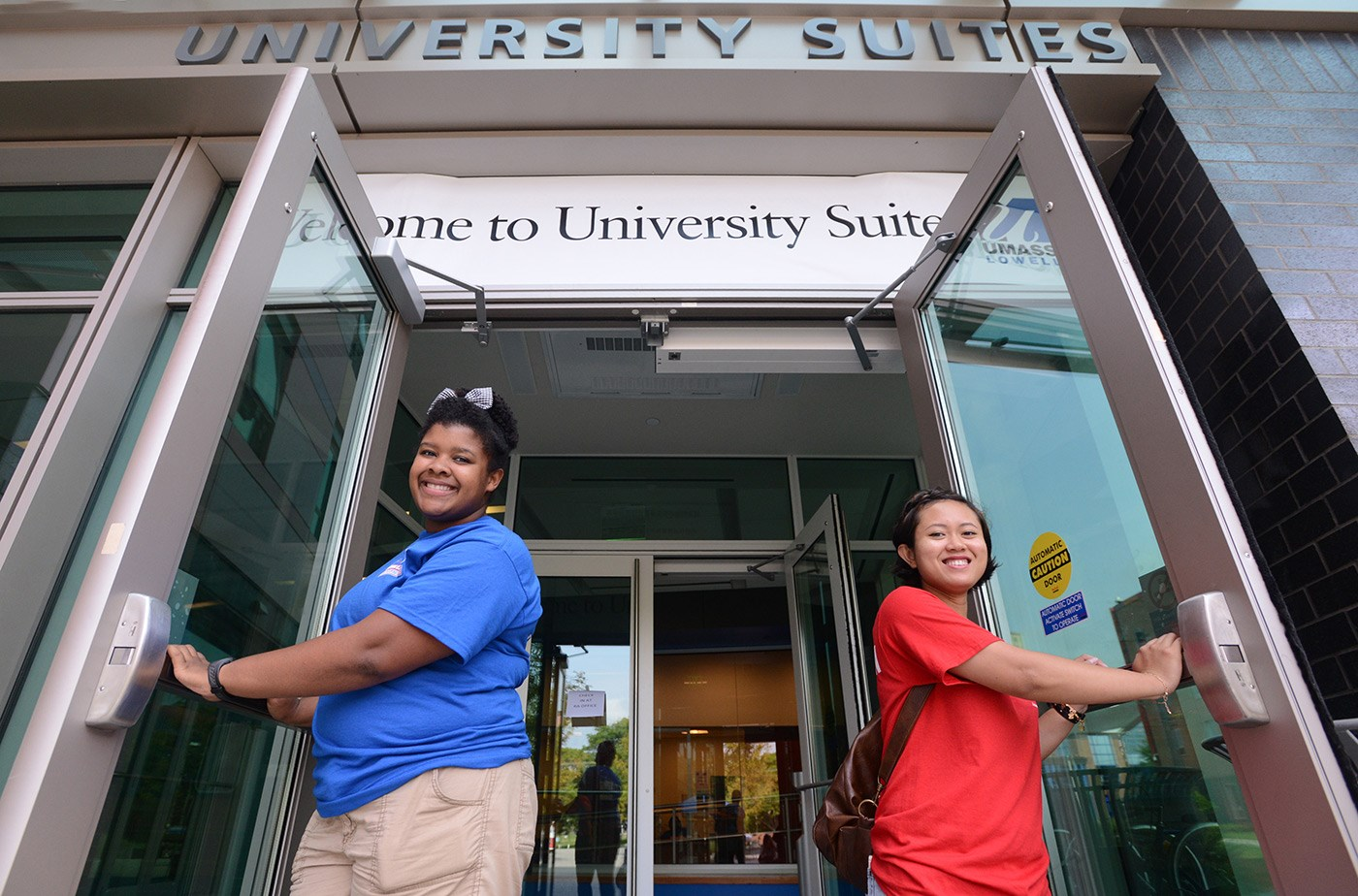 Two Residence Life staffers hold the doors to University Suites open during move-in.