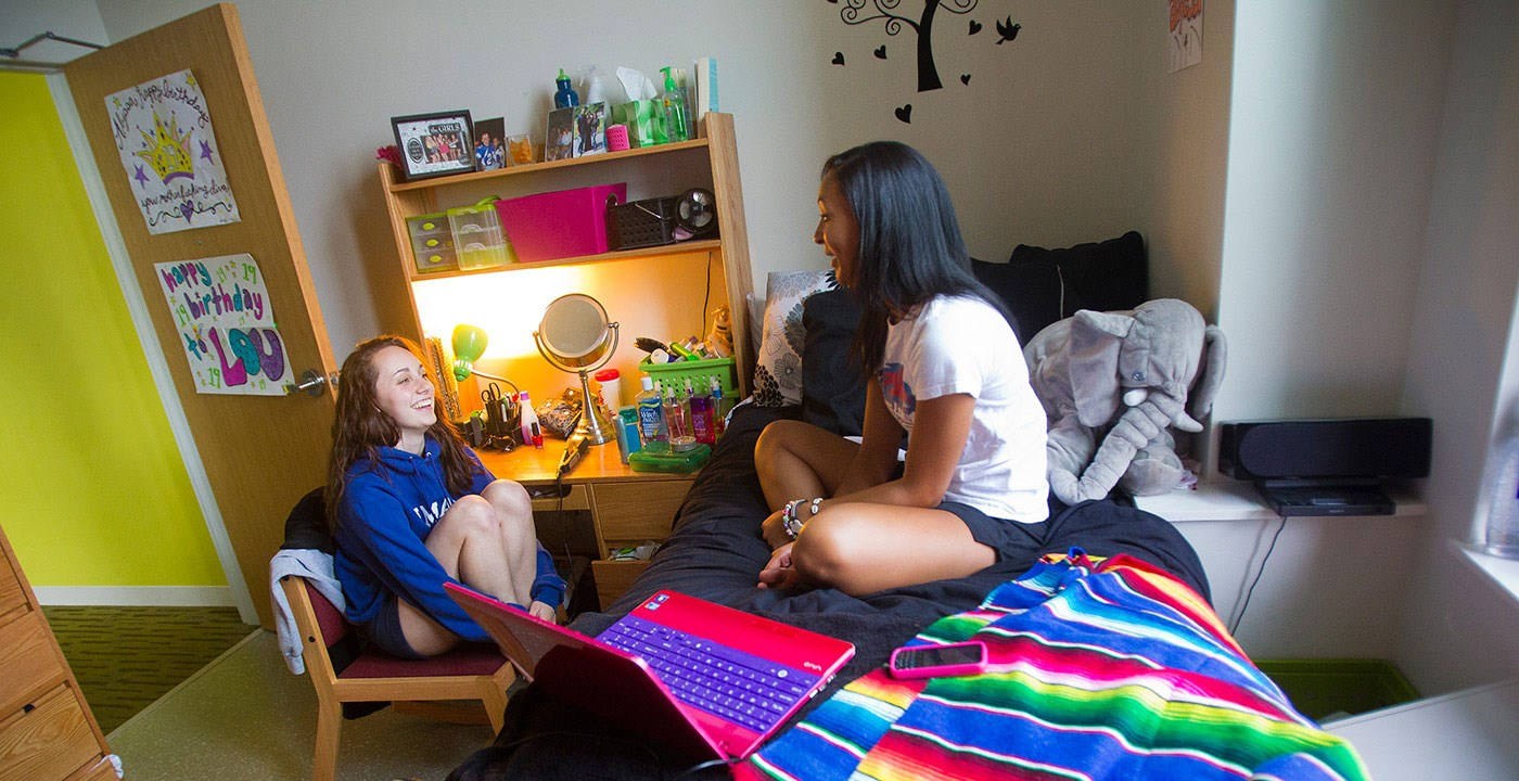 two female students laughing and chilling inside their dorm.