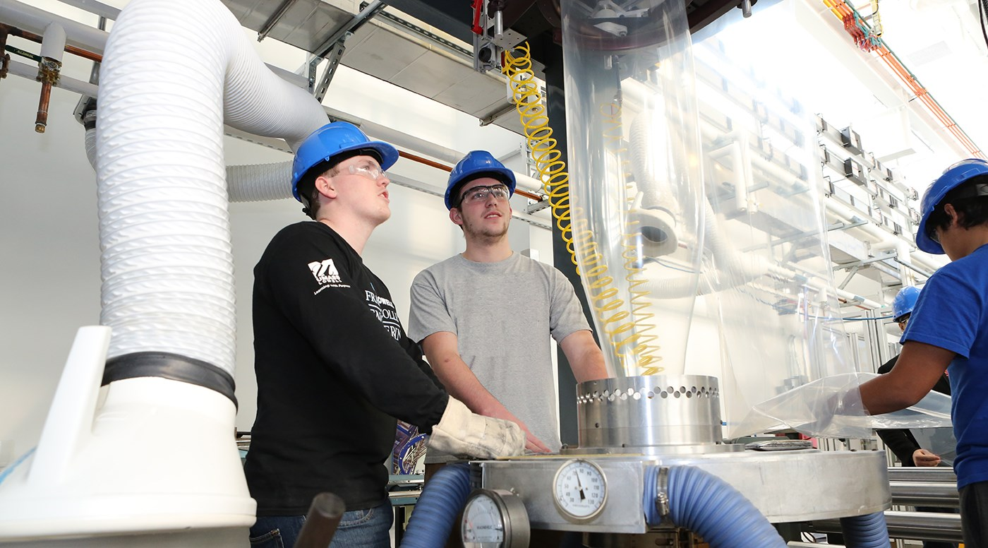 Two male UMass Lowell students wearing hard hats while working in a Plastics recycling lab.