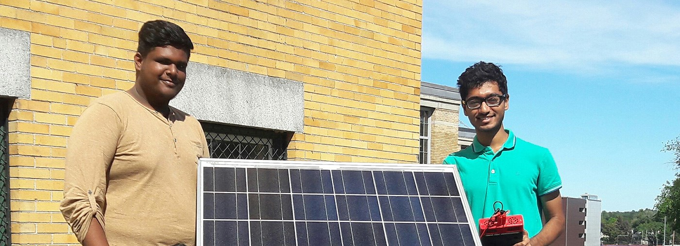 Two UMass Lowell students pose with a solar panel.