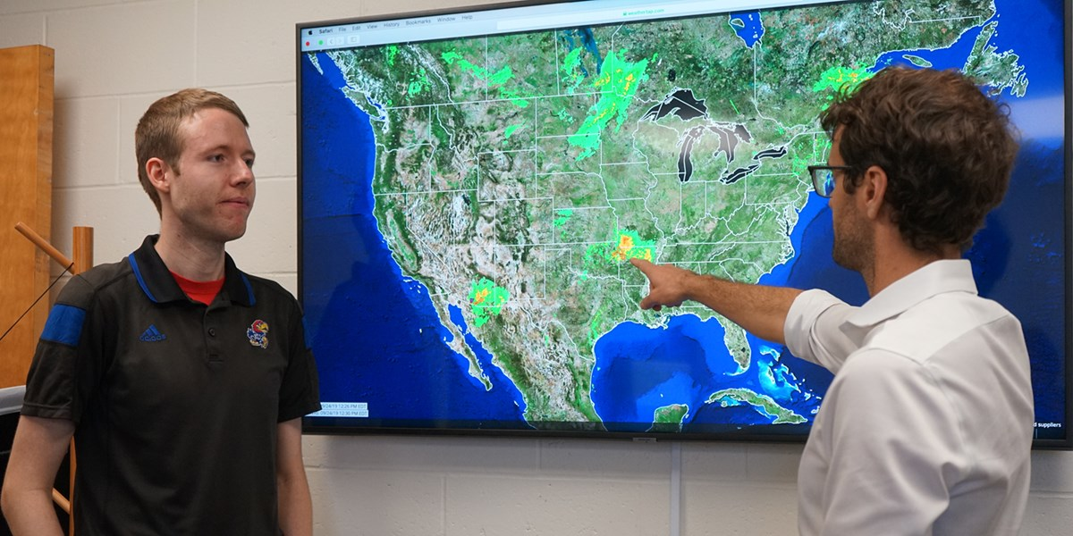 Christopher Skinner points at a weather map on a screen with Tyler Harrison looking on