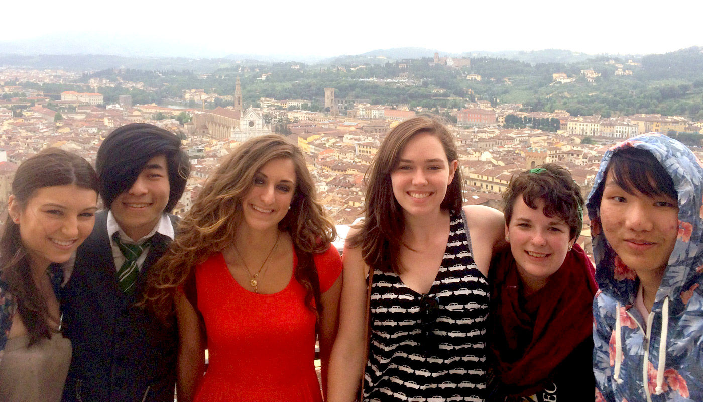 Six Umass Lowell art students, posing in front of a city in a foreign country.
