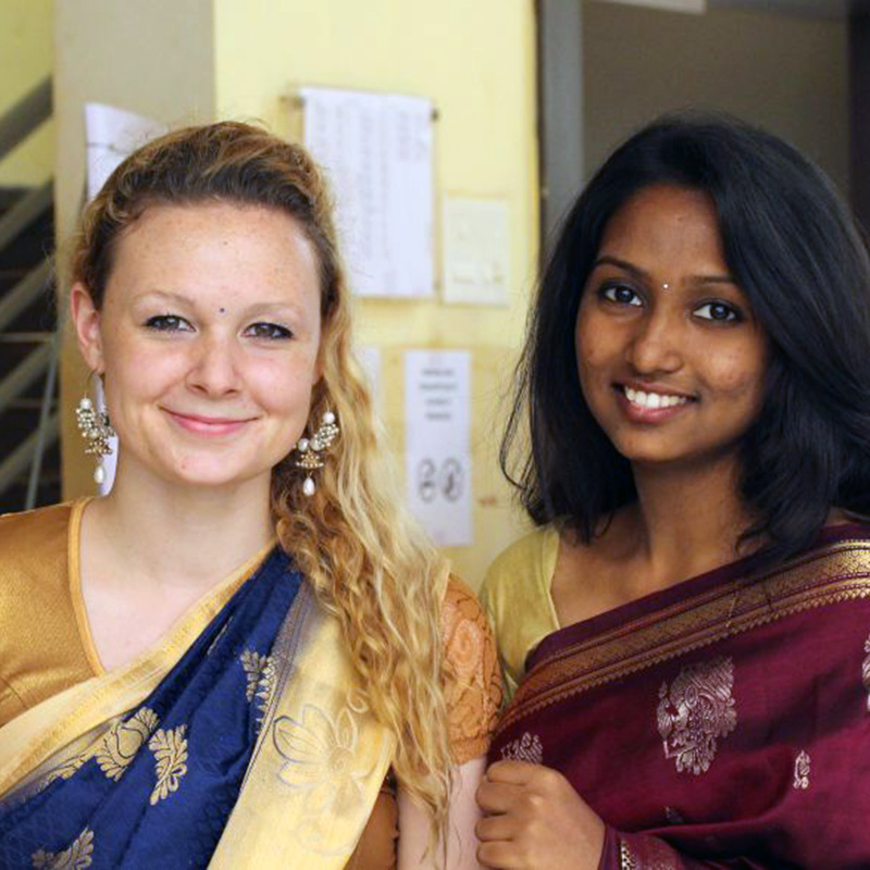 A UMass Lowell student poses with a young Indian woman - both in sarries from 2017-2018 UMass Lowell Winter Study Abroad trip to India. Blog post: The next morning we were woken up to be dressed by the hostel housekeeping women who wear sarries every day. It took them about 15 minutes or so to wrap and pin each of us to their liking. Then some of the Indian girl students did our make up and gave us jewelry.