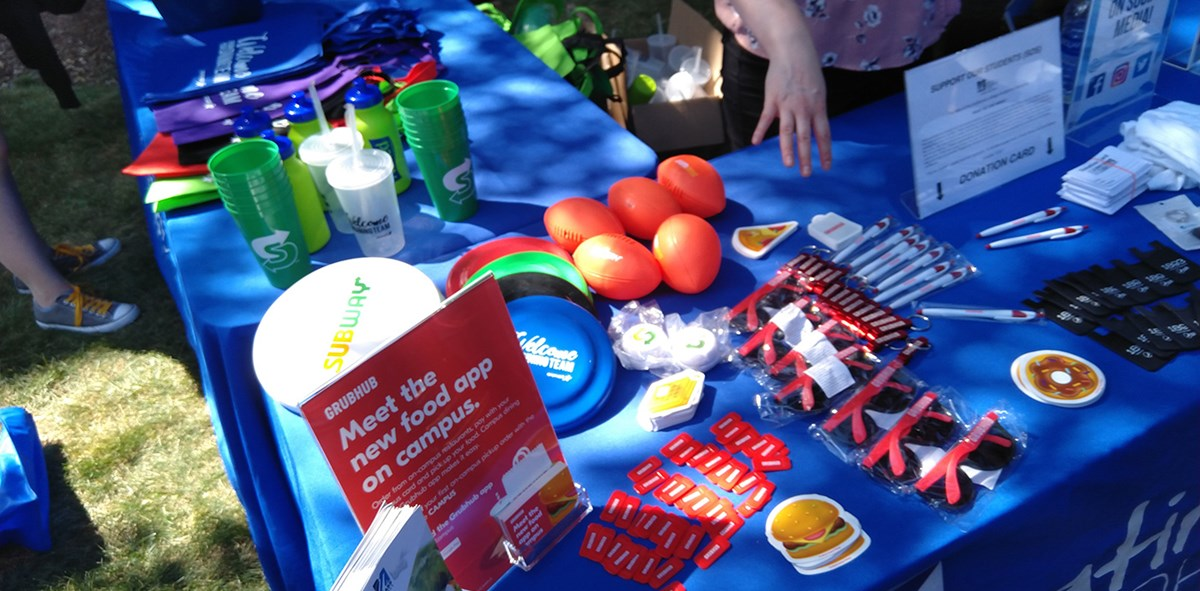 A table displaying UMass Lowell and other vendor branded swag including: frisbees, cups, sunglasses, pens, bags, balls and more.
