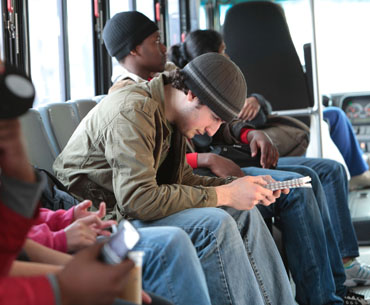 A male student, along side other Umass Lowell students, riding the Umass Lowell Bus.