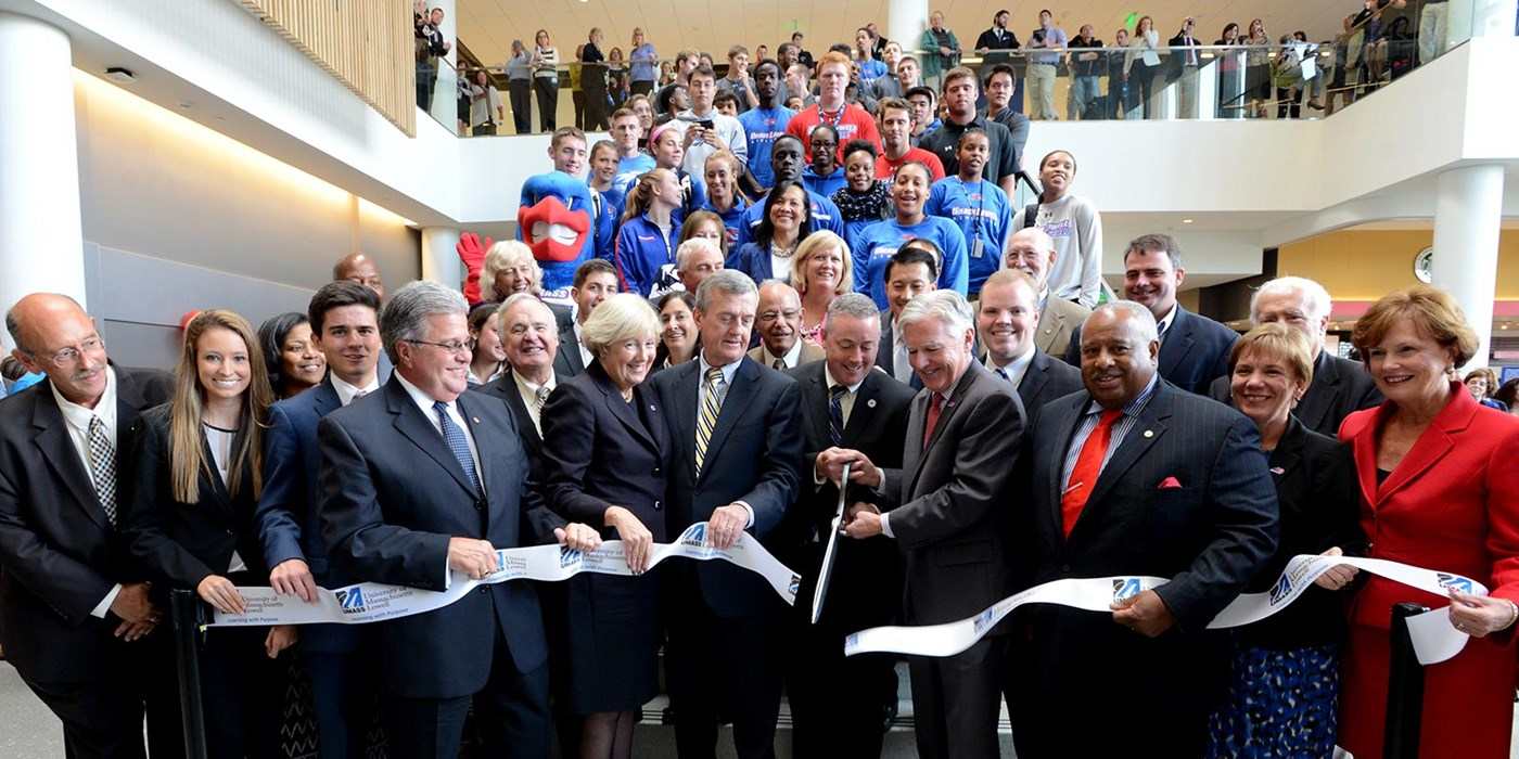 A bunch of Umass lowell members and students gathered to have a grand opening of a building.