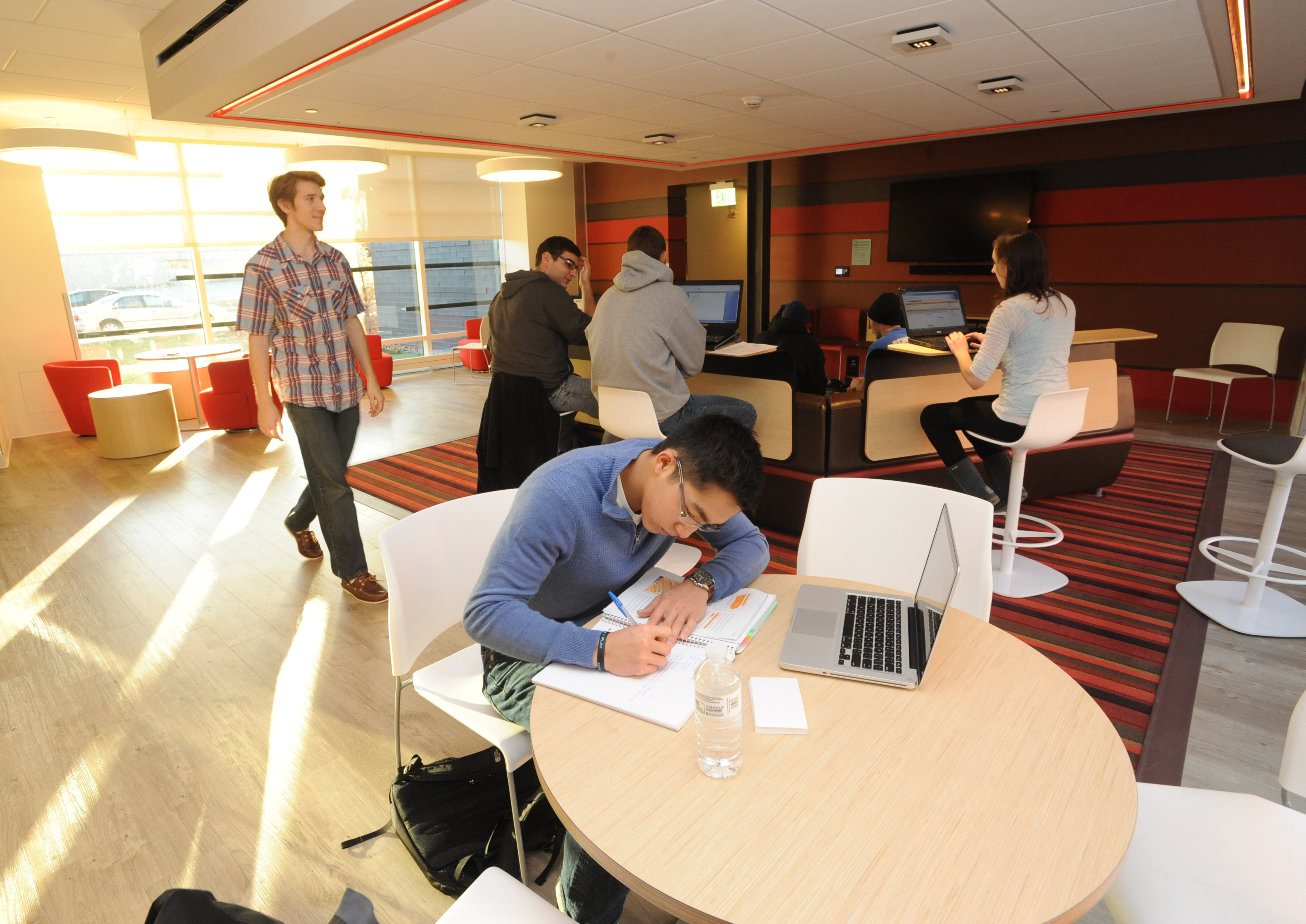 Students work at tables and at bars in sunny common area at University Suites