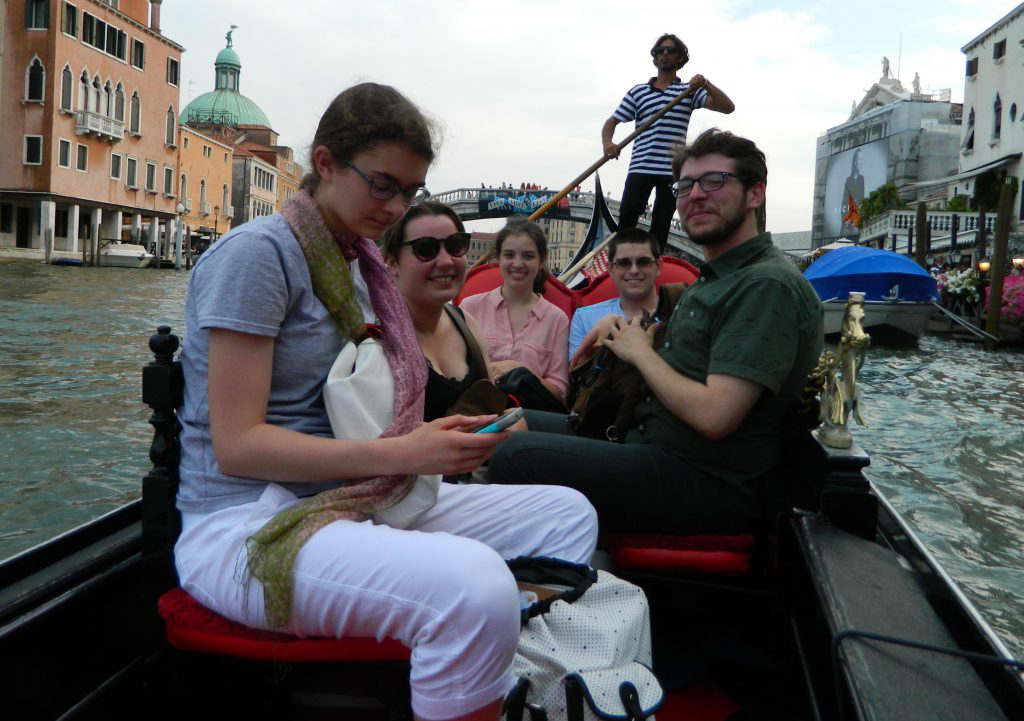 UMass Lowell study abroad students ride a gondola in Venice. Caption: Mass tourism is pushing the locals out of Venice.