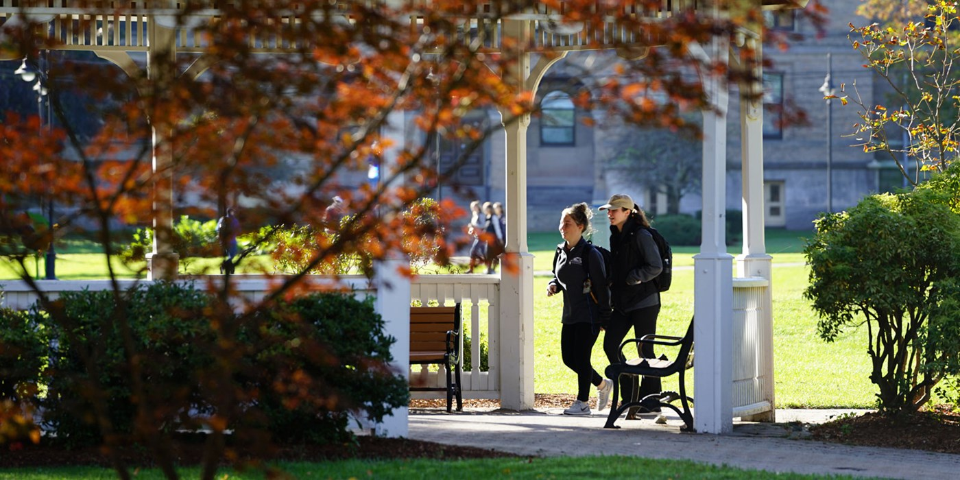 Two women walking under gazebo on south campus