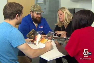Student veterans at UMass Lowell speak around a table.