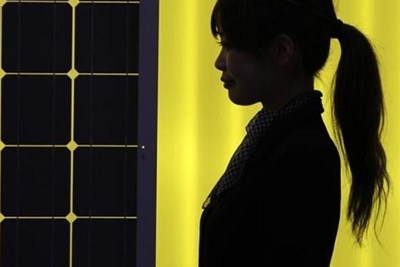 A woman is silhouetted next to a solar panel display.