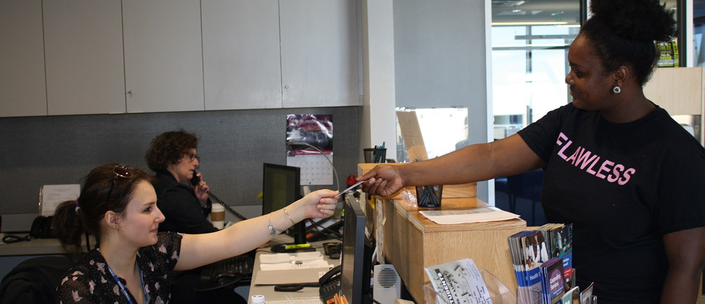 A student handing their ID to the wellness center desk member.