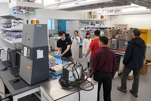 Assoc. Prof. of Chemical Engineering Dongming Xie, second from right, and his research team set up their new lab at the renovated Perry Hall.