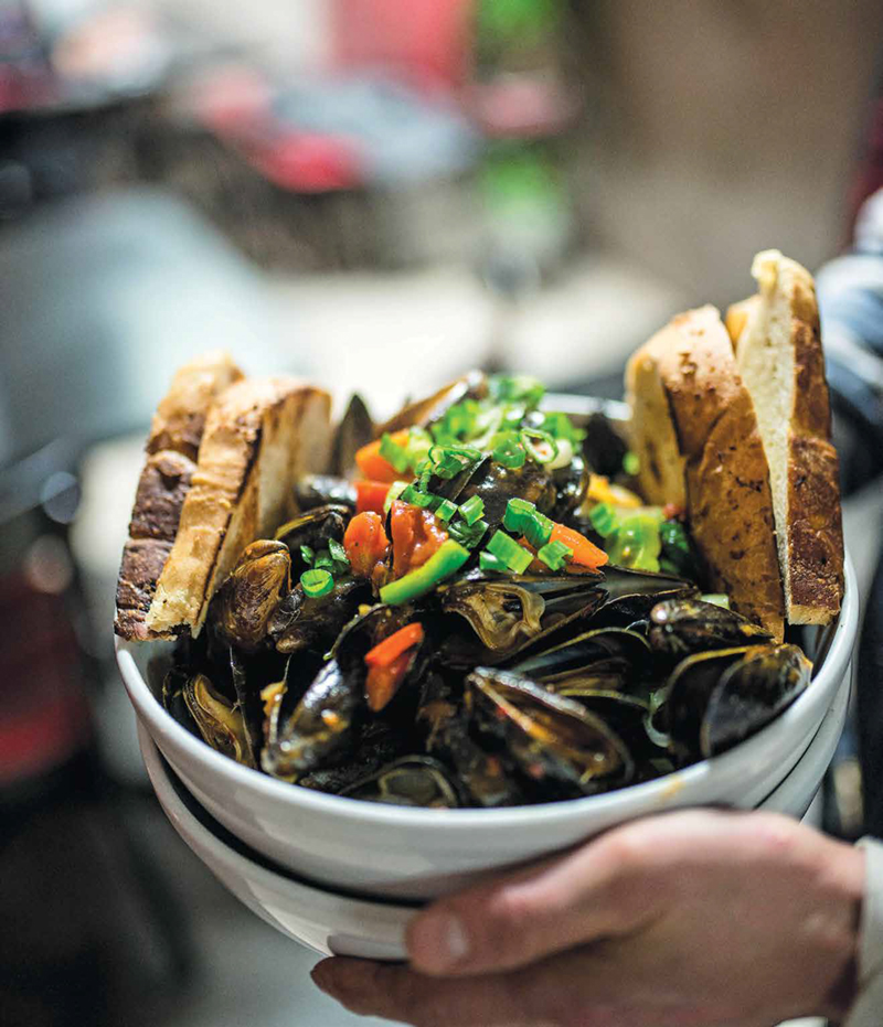 Hands holding a bowl full of mussels and 4 slices of bread from Sizzling Kitchen in Lowell