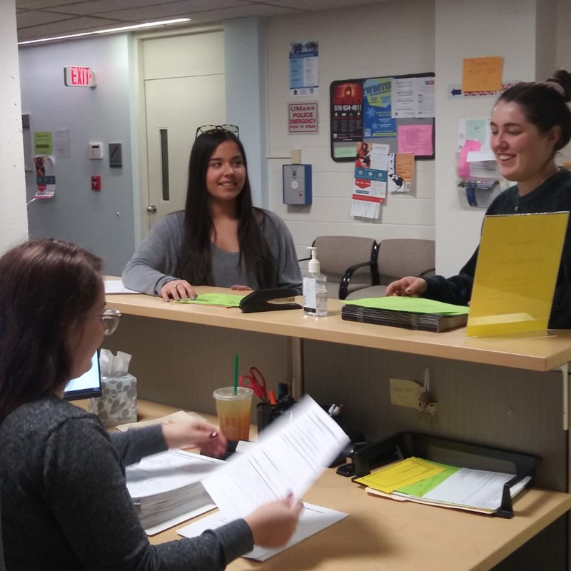 Two students smiling at the front desk of the Writing Center