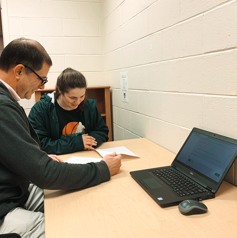 A student gets help with a paper at the Writing Center