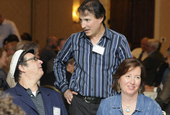 Chris Porter, center, who grew up in Lowell listening to WJUL, catches up with friends at the WUML 60th reunion dinner.