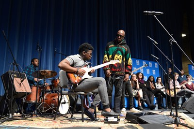 Singer-rapper Wyclef Jean on stage with a UMass Lowell student in Durgin Hall