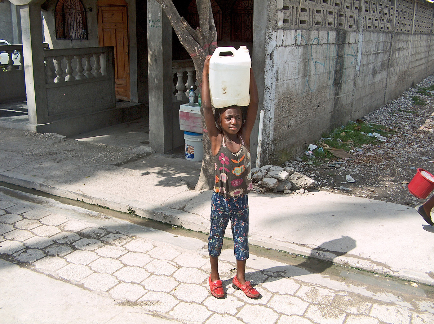 A young girl fetches contaminated water from a community well in Les Cayes, Haiti in 2013.